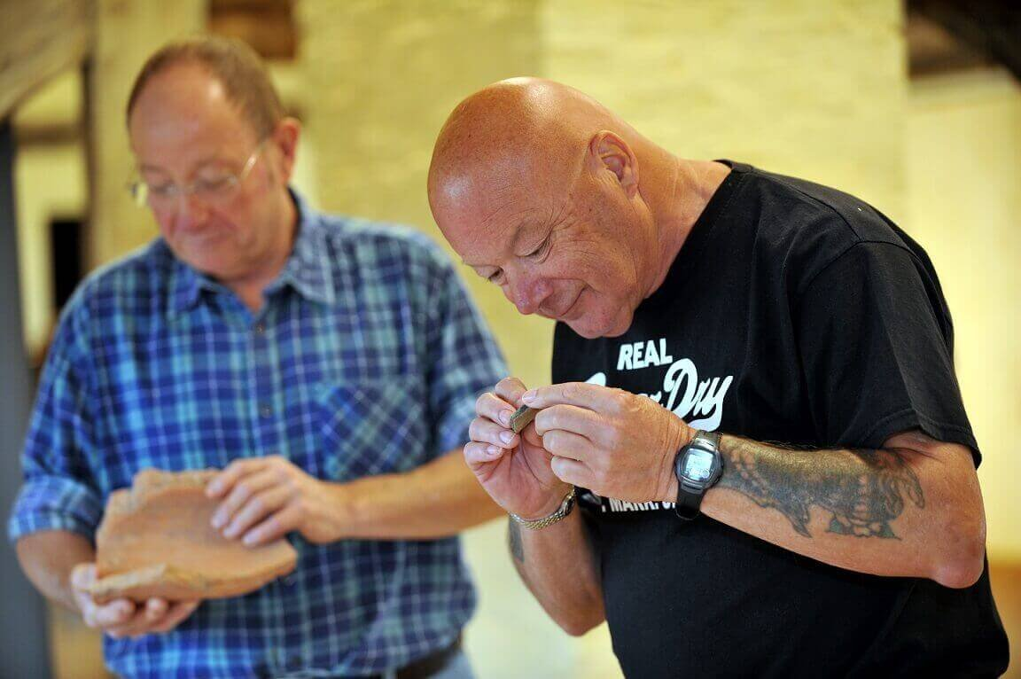 Two gentlemen looking at archaeological finds