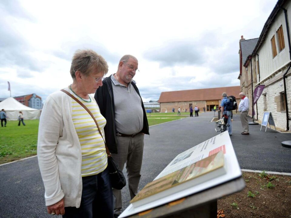 Image of visitors looking at the information boards at Llanthony Secunda Priory
