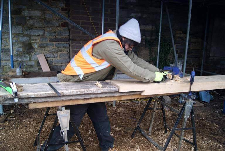 A heritage craft apprentice planes wood as part of placement